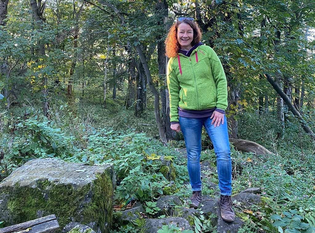 Ellen Langstein steht im Wald auf Steinen - Blogstartbild